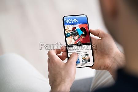 uomo che usa smartphone che legge