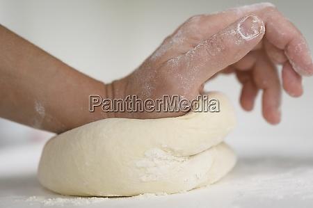 close, up, of, hand, kneading, dough - 29028582
