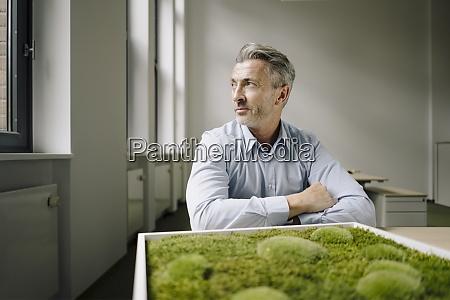 uomo daffari seduto vicino a cornice