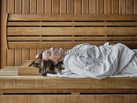 donna anziana sdraiata in sauna di