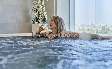 donna felice che beve in piscina